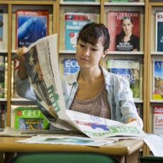 Frau beim Zeitung lesen in der Stadtbibliothek