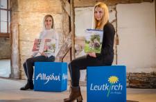 Julia Panzram (links) und Sabrina Schweikart von der Leutkircher Touristinfo präsentieren das druckfrische Gastgeberverzeichnis 2021 / 2022.