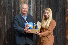 Sabrina Schweikart von der Touristinfo überreicht Hartmut Stiegler als Dank einen Geschenkkorb.