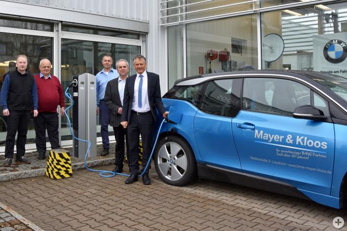 Jürgen Kloos, Hugo Kloos, Thomas Gaile, Herbert Mayer und Oberbürgermeister Hans-Jörg Henle freuen sich über die neue E-Ladestation vor dem Autohaus (v.l.)