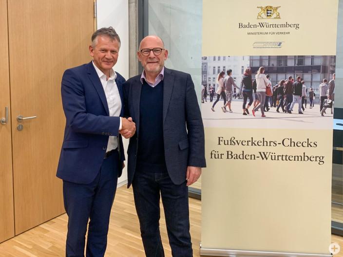 """Verkehrsminister Winfried Herrmann (rechts) gratuliert Oberbürgermeister Hans-Jörg Henle zur Teilnahme an den """"Fußverkehrs-Checks 2019""""."""