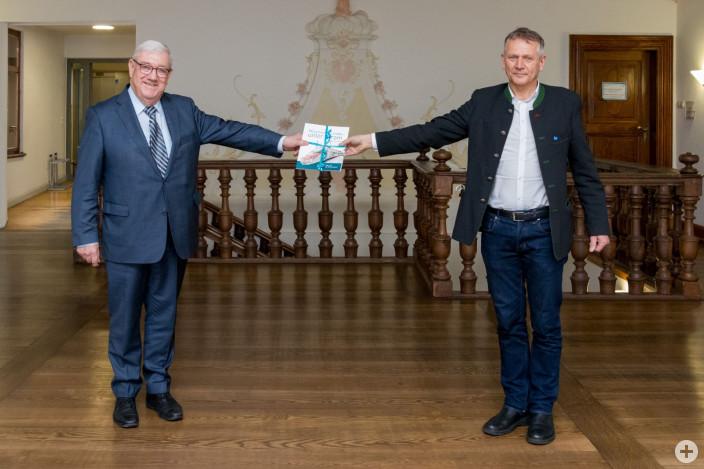 """Josef Miller überreicht OB Hans-Jörg Henle eines der ersten Exemplare von """"München – Lindau unter Strom""""."""